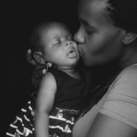 grayscale-photo-of-woman-kissing-child-3704379
